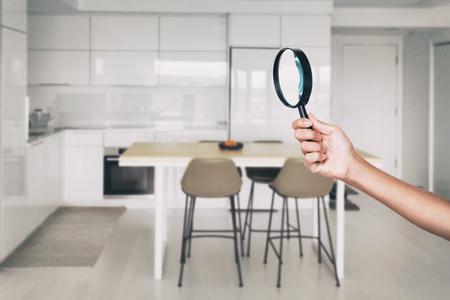 Huisinspectie - vergrootglasinspecteur die de achtergrond van het keukenhuis bekijkt