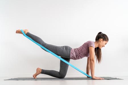 Chica fitness de banda de resistencia haciendo ejercicios de piso de patada de burro de entrenamiento de piernas con correa de goma elástica. Activación de los glúteos con contragolpe para la celulitis.