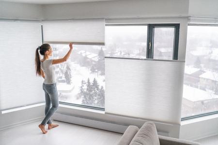 Kobieta otwierając domowe zasłony w miejskim mieszkaniu. Nowoczesne, odgórne i oddolne rolety komórkowe na oknie mieszkania utrzymujące ciepło w zimie z zasłoną o strukturze plastra miodu. Bezprzewodowe plisowane klosze.