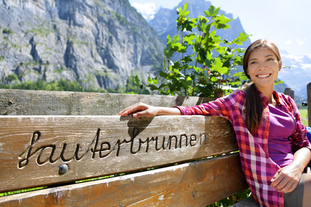 Switzerland Alps summer travel Asian tourist woman smiling relaxing sitting on wooden bench with the word Lauterbrunnen carved in. Europe summer vacation. Stock Photo