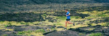 Runner athlete running on volcanic mountain hills incline jumping through rocks exercising cardio man training endurance outdoors banner panorama landscape.