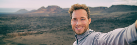 Selfie tourist man hiking in volcano mountain landscape black volcanic rocks. Happy smiling youn adventure hiker in summer travel destination. Banner panorama background. Фото со стока