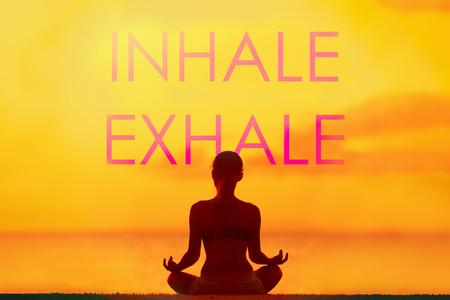 Yoga quote INHALE EXHALE for breathing meditation concept. Silhouette of woman doing yoga meditation on beach background with silhouette of girl meditating in lotus pose. For social media advertising.