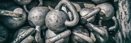 Gym background panorama banner. Crossfit training workout texture of numerous kettlebell weights for weightlifting. Fitness center kettlebells for cross training panoramic.