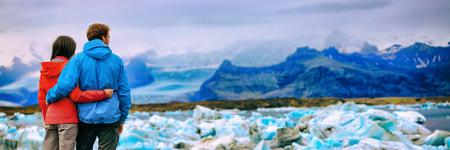 Island-Gletscherlandschaftstouristenpaare am See Jökulsárlón. Winter-Abenteuer-Wandern. Panorama-Banner-Hintergrund.