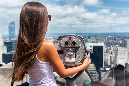 New York City tourist travel woman looking at view of skyline with binoculars from skyscraper rooftop building. Girl traveling in USA summer holidays trip. Stock Photo