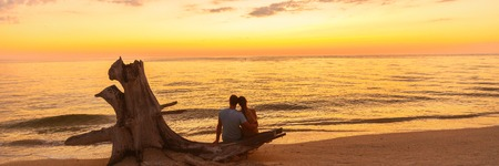 Romantic beach couple honeymoon banner background - Lovers enjoying watching sunset on summer travel destination sitting on tree trunk by the ocean.