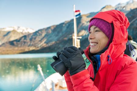 Alaska cruise travel woman looking at wildlife with binoculars. Tourist at Alaska Glacier Bay on ship. Woman on vacation looking at nature landscape enjoying cruising famous tourist destination. Stock Photo