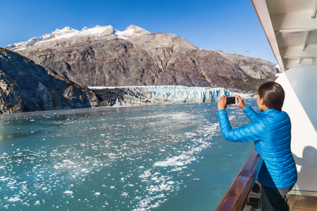 Alaska cruise tourist taking photo of Glacier Bay. Ship passenger on balcony looking at view taking smartphone pictures of Margerie glacier from boat. Woman using phone app on travel vacation. Stock Photo
