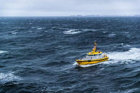 Barco de patrulla de la guardia costera cabalgando sobre las olas del mar embravecido en Alaska.