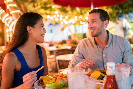 Couple eating hamburgers at outdoor restaurant terrace happy tourists on summer vacation. Florida travel people eating food at night during holidays in Miami. Asian Caucasian interracial young adults.