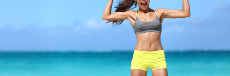 Strong fitness woman banner crop with copyspace on sky. Body crop of athlete showing off slim body on beach. Weight loss success concept. Stock fotó