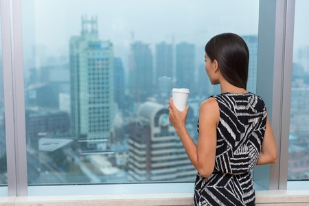 Business woman drinking coffee in office during lunch break looking at city's skyline view from window thinking, Shanghai, China.