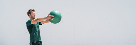 Banner. Medicine ball workout fitness man strength training arms doing front raise exercise for shoulder muscles. Upper body weighted ball workout at fitness centre. Panorama crop with copy space.