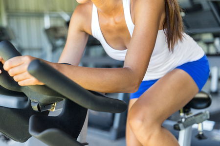 Woman doing HIIT cardio workout in indoors gym bike. Woman cyclist working out biking interval training on indoor bicycle.