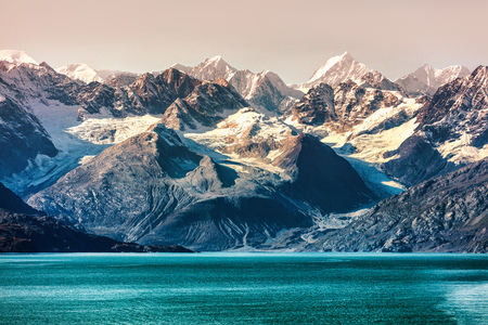 Glacier Bay National Park, Alaska, USA. Alaska cruise travel view of snow capped mountains at sunset. Amazing glacial landscape view from cruiseship vacation showing snowy mountain peaks. Stock Photo