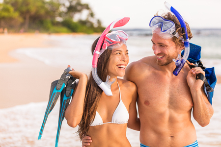 Happy couple laughing together beach fun on summer snorkel travel vacation healthy active lifestyle. Sports leisure young friends doing snorkelling swim activity at Hawaii tropical holidays. Stock Photo