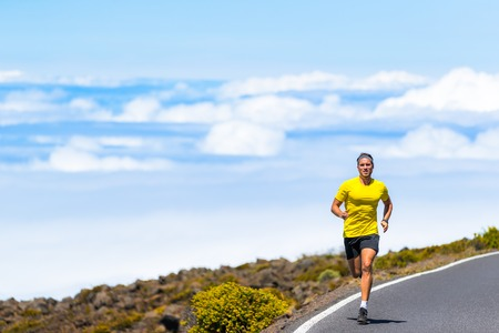 Sports man running on road training for marathon in nature landscape outdoors.