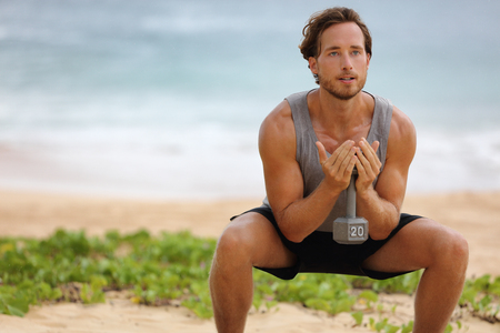 Fitness man training squat with dumbbell weight doing exercise for glutes muscles and quads, working out legs on beach.