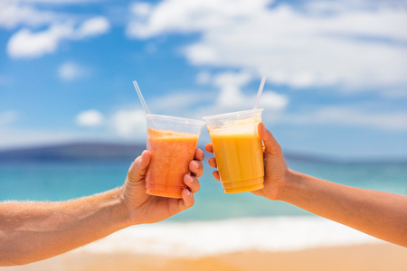 Couple toasting healthy juice drinks together at beach restaurant. Detox smoothie drink toast at summer vacations holidays. Fruit juicing weight loss diet. Foto de archivo - 117700941