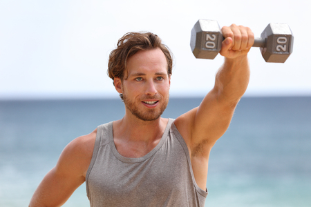 Fitness man lifting dumbbells on beach doing Front Dumbbell Raise i.e. Alternating Front Raise workout for shoulders. Exercising male fitness model working out outside.