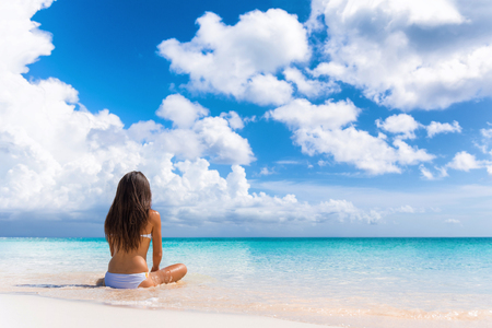 Beach luxury travel woman relaxing on summer vacation at spa retreat resort sitting enjoying ocean view meditating. Wellness relaxation holiday.