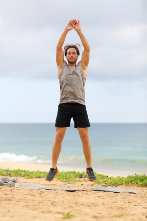 Jump Squats fitness training. Athlete Man doing Jump Squat exercise workout. Male fitness instructor training on beach.