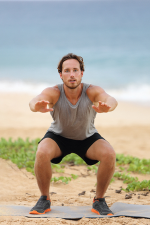 Squat exercise fitness man training squats for glutes and quadricep muscles doing workout burpees working out beach in summer outdoors.