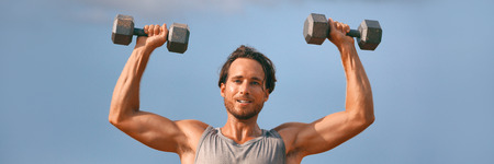 Fitness gym banner man lifting dumbbell weights. Panorama horizontal crop with copy space of athlete with muscular arms with dumbbells overhead training biceps. Stok Fotoğraf