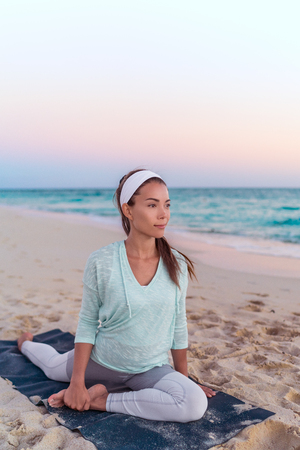 Yoga woman stretching legs doing pigeon pose leg stretch on beach at morning sunrise. Fitness healthy lifestyle.