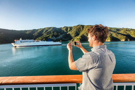 Cruise travel man tourist taking phone picture of ferry boat cruising on sea. Tourism photos during New Zealand island crossing holiday at Marlborough sounds Cook strait. Stok Fotoğraf