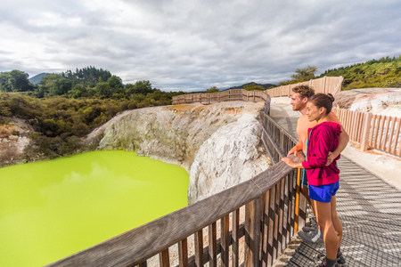 New Zealand travel tourists looking at green pond. Tourist couple enjoying famous attraction on North Island, geothermal pools at Waiotapu, Rotorua. Stockfoto