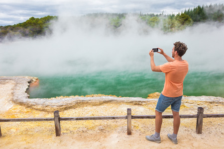New Zealand travel tourist taking phone picture of famous attraction Champagne pool, Waiotapu. Active geothermal area, Okataina Volcanic Centre, Reporoa, in Taupo Volcanic Zone, Rotorua, north island. Stockfoto
