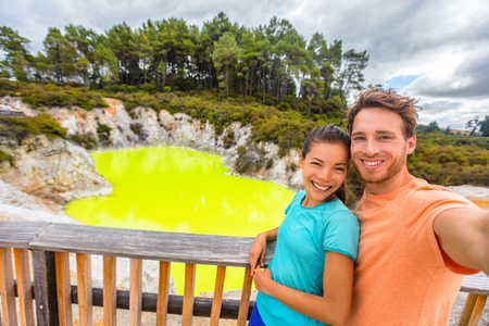 New Zealand tourist attraction couple tourists taking selfie travel destination, Waiotapu. Active geothermal green pond, Rotorua, north island. Stock Photo