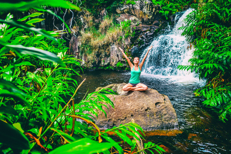 Yoga nature wellness meditation retreat woman at tropical waterfall forest in Kauai, Hawaii. Happy girl with open arms in serenity enjoying lush outdoors, mindfulness concept.