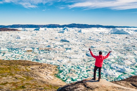 Greenland hiking travel tourist man with arms up winning at icebergs and frozen ice floating in ocean sea. Arctic nature landscape. adventure in the outdoors. Stock Photo