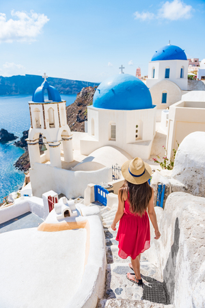 Travel Europe tourist girl walking in Santorini stairs of city streets, famous european destination three blue domes, famous Greek landmark. Oia village, Santorini island, luxury vacation. 免版税图像