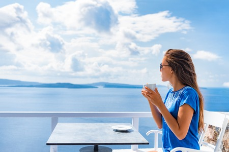 Tranquil morning serene woman relaxing drinking breakfast coffee enjoying ocean sea view on luxury hotel balcony, summer travel holidays. Home living. Stock Photo