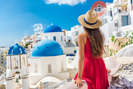 Europe holiday Santorini vacation girl in hat and red dress enjoying view of 3 blue domes famous tourist attraction in Europe. Summer sun holiday.