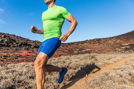 Trail runner ultra running man athlete on desert path in dry heat landscape. Male sports person training outdoors. Closeup of body and legs.
