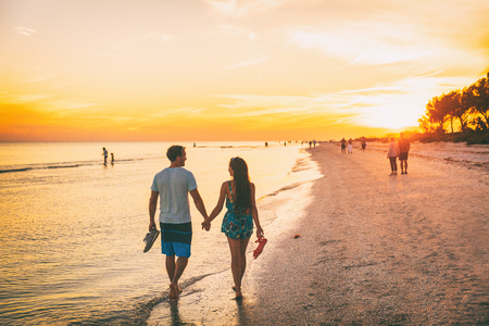 Beach summer beach people lifestyle happy couple enjoying sunset walk on Shelling beach famous tourist destination on the southwest coast of Florida -Gulf of Mexico. Sanibel Island, Florida.