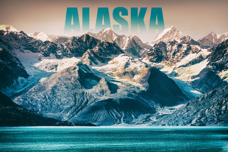 Alaska Glacier Bay landscape National Park, USA. Alaska text written as title above mountain top for cruise destination. Background of snow capped mountains peaks at sunset winter vacation. 免版税图像