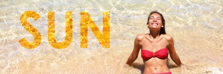 Sun travel vacation in the tropical Caribbean woman sun tanning with the word SUN written on the sand texture background for advertisement concept. Banner panorama crop.