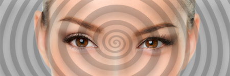 Hypnosis spiral over eyes of woman hypnotized closeup banner panorama. Asian girl portrait background. Stock Photo