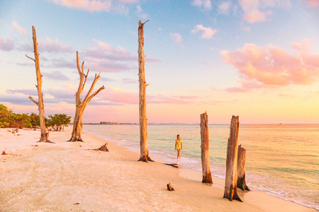 Lovers key beach in the gulf of Mexico, Florida travel destination. Woman relaxing watching sunset walking in ocean water on american beach. Southwest Florida. Stock Photo