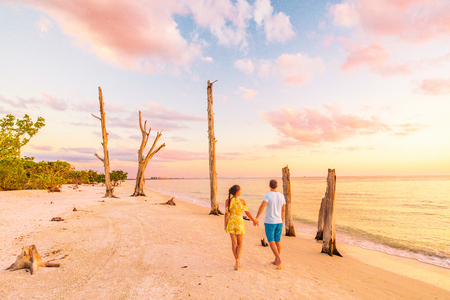 Couple walking on beach at sunset romantic travel getaway, idyllic Florida destination, Lovers key beach state park in the gulf of Mexico. Woman and man holding hands relaxing. Southwest Florida.