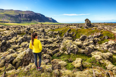 Iceland travel - woman walking hiking on lava fields in Iceland covered in moss - amazing nature landscape. Summer travel.