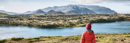 Iceland hiking travel adventure - woman tourist walking in mountain landscape looking at amazing view of nature, panorama banner.