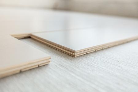 Instalación de piso de madera de ingeniería con membrana de contrapiso en el condominio. Primer plano de tablones de madera de arce mostrando capas de madera contrachapada compuesta. Concepto de remodelación de mejoras para el hogar. Foto de archivo