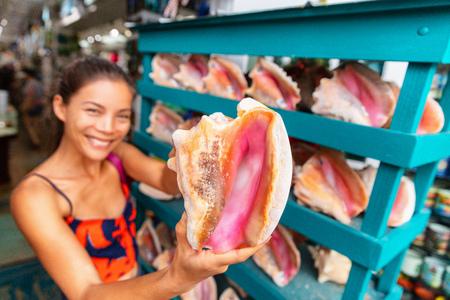 Souvenir shop selling conch shells seashells store in Florida, USA travel, Asian tourist woman buying seashell.
